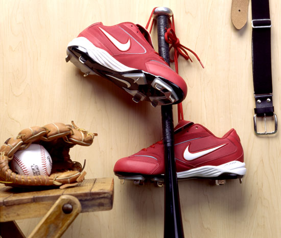 Cleats hanging from baseball bat in locker room